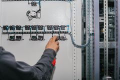 Electrician specialist checking low-voltage cabinet equipment. Photo of male electrical technician specialist checking indoor electric low-voltage cabinet Stock Images