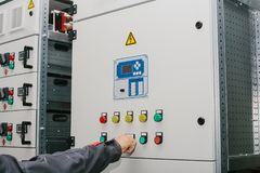Electrician specialist checking low-voltage cabinet equipment. Photo of male electrical technician specialist checking indoor electric low-voltage cabinet Stock Image