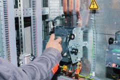 Electrician specialist checking low-voltage cabinet equipment. Photo of male electrical technician specialist checking indoor electric low-voltage cabinet Royalty Free Stock Photo