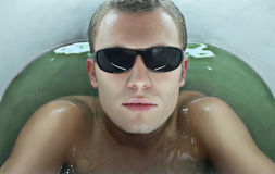 Photo of male face. With sunglasses. In the green water royalty free stock image
