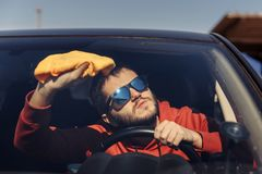 Photo of male with orange rag washing windshield. Of car royalty free stock image