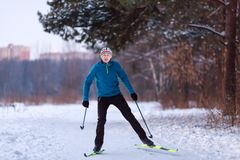 Photo of male skier in blue jacket in winter park. On background of houses Stock Photography