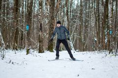 Photo of male skier in gray jacket. In winter forest Stock Photography