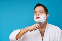 Photo of male in white coat shaving. On empty blue background stock photo