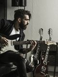 Man playing his electric guitar in a music studio. Photo of a man with beard sitting and playing his electric guitar in a recording studio stock photo