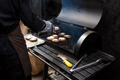 Photo of man cooking burgers on big grill Royalty Free Stock Photo