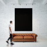 Photo of man in gallery. Waching black empty canvas hanging on the brick wall and vintage classic sofa wood floor Stock Image