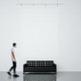 Photo of man in gallery. Waching empty canvas hanging on the brick wall and black generic design sofa concrete floor. Photo of man in gallery. Waching empty Royalty Free Stock Photo