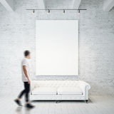 Photo of man in gallery. Waching empty canvas hanging on the brick wall and vintage classic sofa wood floor. Square Royalty Free Stock Photography
