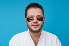 Photo of man with gel pads under eyes and in white robe. On empty blue background stock photos