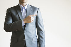 Photo of a man in grey suit pointing at empty space next to him.  Royalty Free Stock Photos