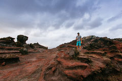 Photo of Man With Grey Top and Teal Shorts in Brown and Grey Rock Mountain Stock Photography
