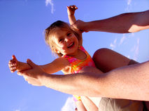 Airplane Child. Photo of a man holding up a child doing the airplane pose Royalty Free Stock Photo