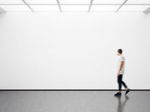 Photo of man in modern gallery looking at the empty canvas. Blank mockup, motion blur Stock Photo