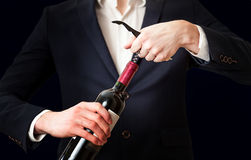 Photo of man opening bottle of wine with corkscrew. Closeup photo of man opening bottle of wine with corkscrew stock photos
