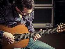 Guitarist playing acoustic guitar in studio. Photo of a man playing his acoustic guitar in a rehearsal studio. Focus on man's head Stock Photography