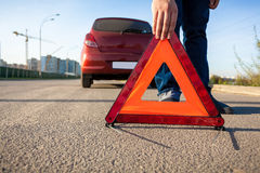 Photo of man putting triangle warning sign on road Royalty Free Stock Image