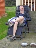 Man relaxing in deckchair on holiday beach hut stock photos