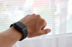 Man`s hand with black smart watch in office. Photo of Man`s hand with black smart watch in office stock photos