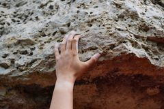 Photo of man`s hand clambering over rock. On summer day stock photos