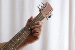 Photo of man`s hand playing acoustic guitar, close-up. Photo of man`s playing tuning guitar, close-up Royalty Free Stock Photos