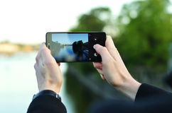 Photo of a man`s hands holding phone and taking photo of a river. With blurred trees and water in the background stock photo