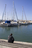 Photo of a man on the sea port,watching to the sailing boats Royalty Free Stock Images