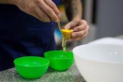 Photo of a man separating eggs. Close up photo of a man separating eggs, cooking, kitchen, bowl, green, yolk, white, chef, handmade royalty free stock photo