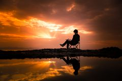 Photo of Man Sitting on Camping Chair During Dawn stock image