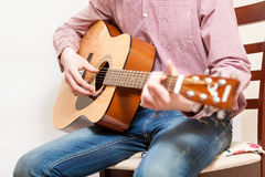 Photo of man sitting on chair and playing on acoustic guitar Stock Images