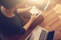 Photo of man touching screen Of generic design tablet holding in his hands. Laptop on the floor. Horizontal Stock Images