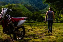 Man walking away from dirt bike in Guatemalan mountains royalty free stock image