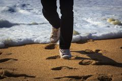 Photo of a man walking on the beach stock photography