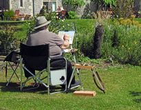 Artist painting on canvas watercolour outdoor summer hobby. Photo of a man wearing a summer hat with paints and brushes painting a garden scene located at royalty free stock photos