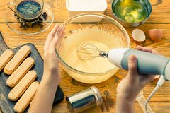 Photo of man with whisk preparing dessert of cookies. Yolks of cream cheese on wooden board royalty free stock photos