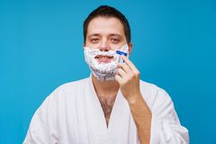 Photo of man in white coat shaving loocing at camera. On empty blue background royalty free stock photos