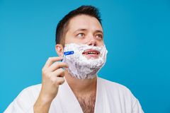 Photo of man in white coat shaving. On empty blue background stock photography