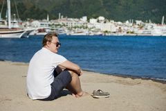 Photo of Man in White Shirt and Blue Short Sitting on Seashore stock photo