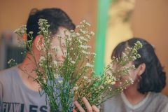 Photo of Man and Woman Behind the Flowers Stock Images