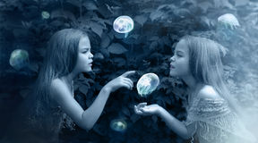 Photo manipulation in blue with girls and jellyfish Stock Photos