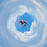 Photo manipulation with spherical panorama of a man free falling. Jumping into the unknown, supported by fluffy clouds Stock Photography
