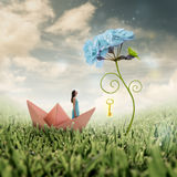Photo manipulation: unlocking the power of individual potential. Black haired young woman looks up at a blown up flower with a parrot and a golden key hanging vector illustration