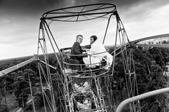 Photo of married couple riding on ferris wheel Stock Images