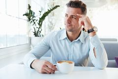 Photo of masculine man 30s sitting alone in city cafe with cup o. F coffee beverage and looking aside in window with brooding sight Royalty Free Stock Image