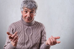 A photo of mature man dressed in sweater standing over white background having surprised expression holding his hands in front of Stock Photos