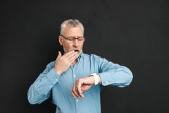 Photo of mature unshaved man 60s with grey hair wearing eyeglass. Es looking at his wrist watch with confusion isolated over black background Stock Photo