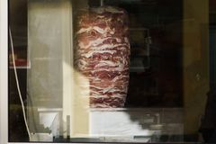 Photo of meat for shaurma cooking behind glass. Of store Stock Photo