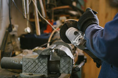 Photo of mechanic grinding a metal plate in workshop. Photo of mechanic grinding metal plate in workshop Royalty Free Stock Photos