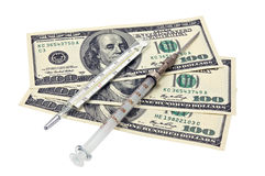 Photo of a medical syringe and paper money Royalty Free Stock Images