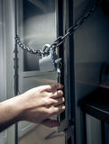 Photo of men hand opening fridge locked by chain Royalty Free Stock Photos